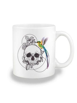 Biały kubek ceramiczny z nadrukiem w stylu boho, przedstawiającym kolorowego kolibra siedzącego na czaszce. Nadruk dwustronny.