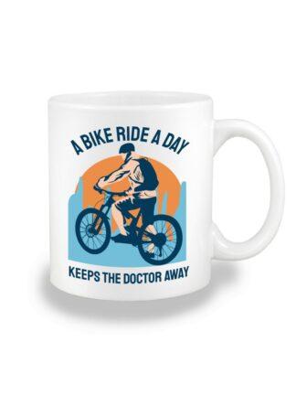 Biały kubek ceramiczny z kolorowym nadrukiem kolarza MTB oraz napisem A Bike Ride A Day Keeps The Doctor Away.