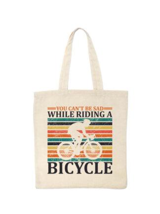 Ekotorba bawełniana w kolorze ecru z nadrukiem kolarza szosowego na tle kolorowych pasów. Całość opatrzona napisem You Can't Be Sad While Riding A Bicycle.
