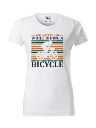 Biała koszulka damska z krótkim rękawem i nadrukiem kolarza szosowego na tle kolorowych pasów. Całość opatrzona napisem You Can't Be Sad While Riding A Bicycle.
