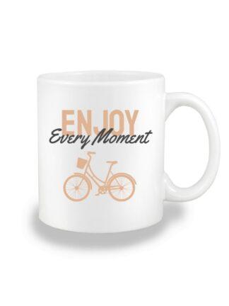 Biały kubek ceramiczny z beżowo-grafitowym napisem Enjoy Every Moment oraz rysunkiem roweru miejskiego.