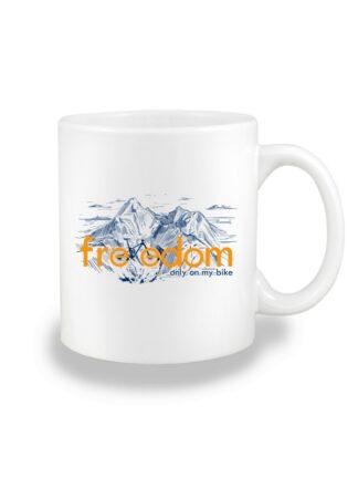 Biały kubek ceramiczny z granatowym nadrukiem roweru MTB wkomponowanym w napis Freedom. W tle rysunek kreskowy wysokich gór.
