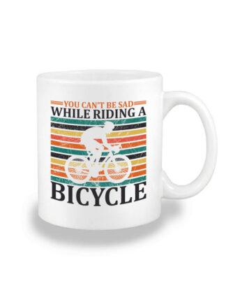 Biały kubek ceramiczny z nadrukiem kolarza szosowego na tle kolorowych pasów. Całość opatrzona napisem You Can't Be Sad While Riding A Bicycle.